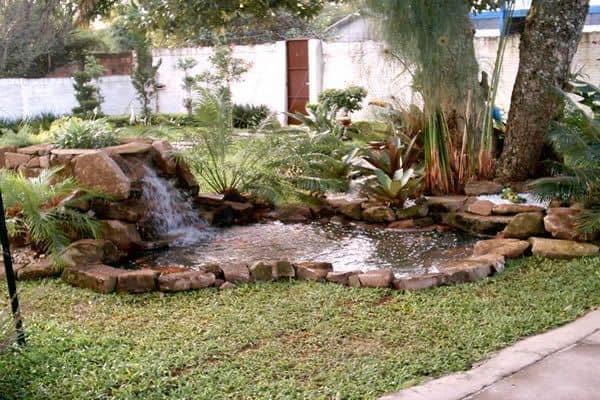 jardim externo gramado com cascata e mini lago