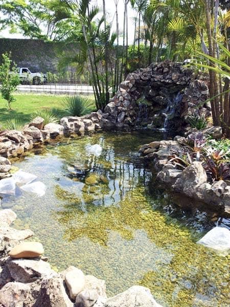 jardim com lago artificial e cascata feita de pedras