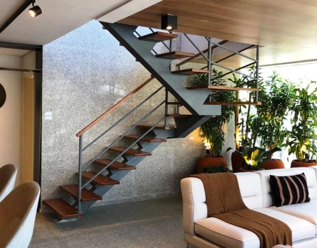 sala com escada espinha de peixe com estrutura de ferro e degraus em madeira