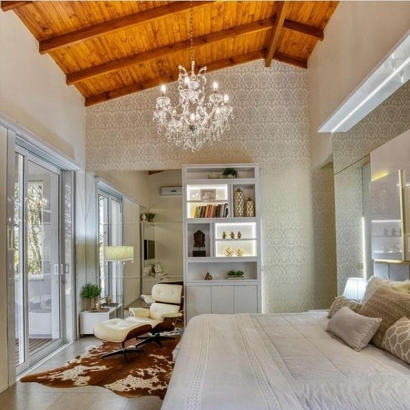 quarto decorado com poltrona Charles Eames branca com puff