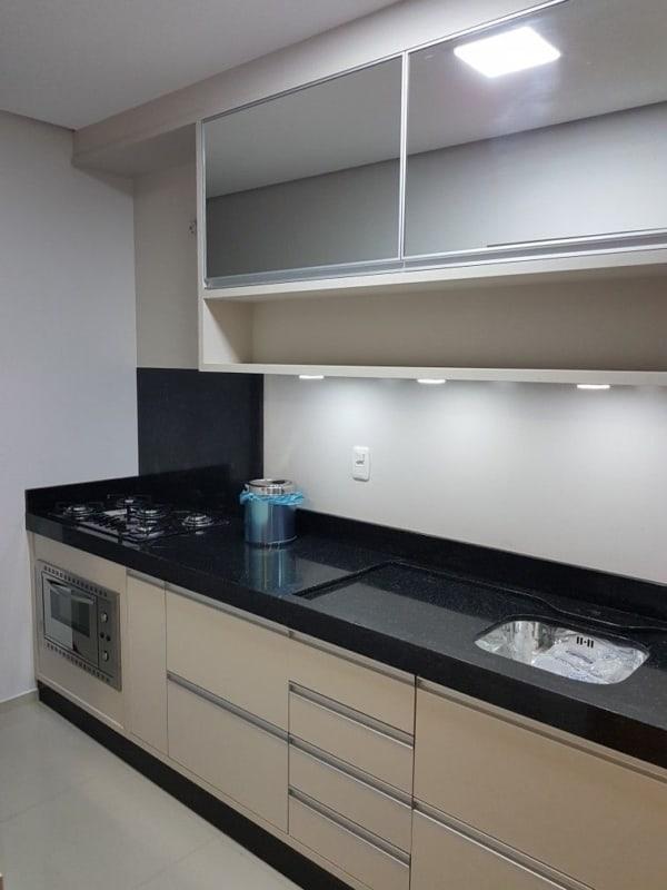 cozinha com armarios areia e bancada preta