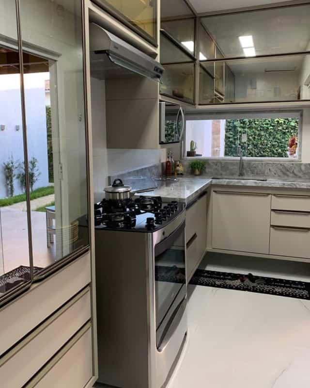cozinha moderna com armarios cor areia e vidro reflecta
