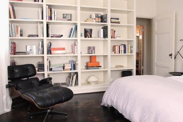 quarto com poltrona Charles Eames preta com puff