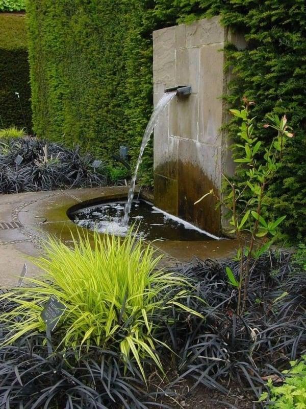 jardim com pequena cascata na parede