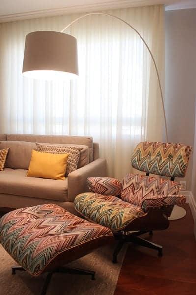sala com poltrona Charles Eames estampada com puff