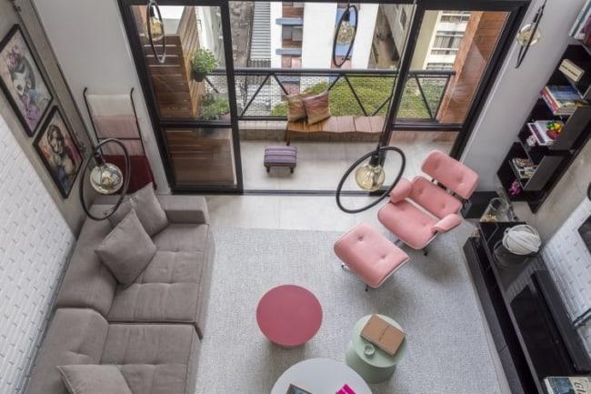 sala decorada com poltrona Charles Eames rosa com puff