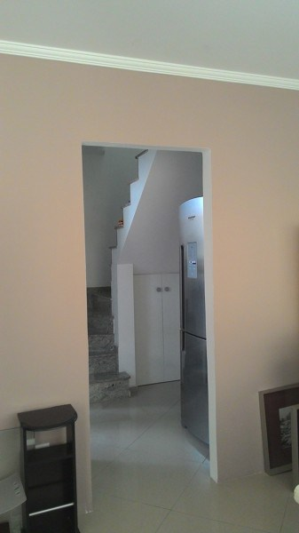 Casa com comodos mesclados entre branco e camurca