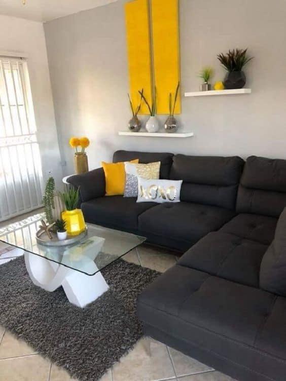 Sala com parede branco gelo sofa preto e acessorios em amarelo
