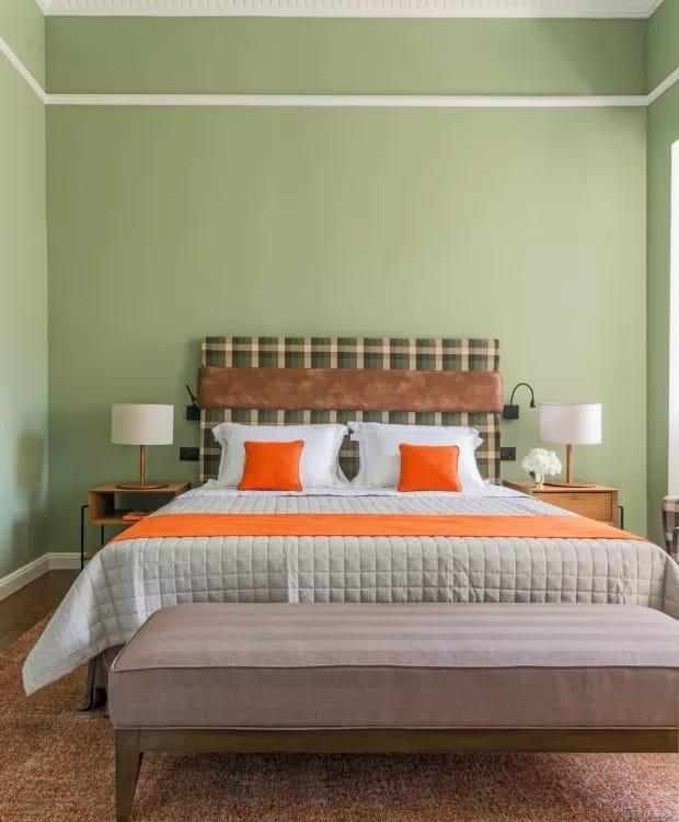 quarto de casal com parede verde e detalhes em laranja