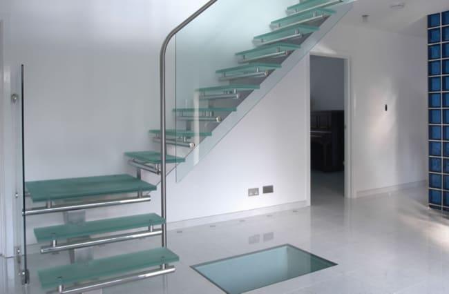 escada em L com estrutura de metal e degraus de vidro jateado