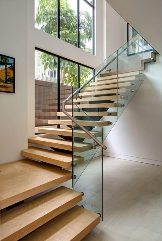 escada em L com degraus em madeira e guarda corpo de vidro