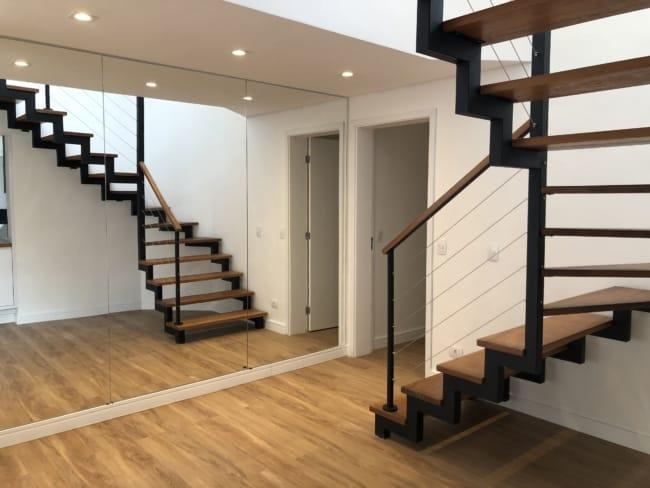 escada moderna em L com estrutura de ferro e degraus de madeira