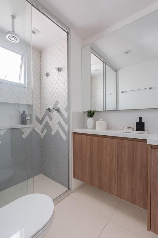 banheiro com revestimentos em cinza e branco