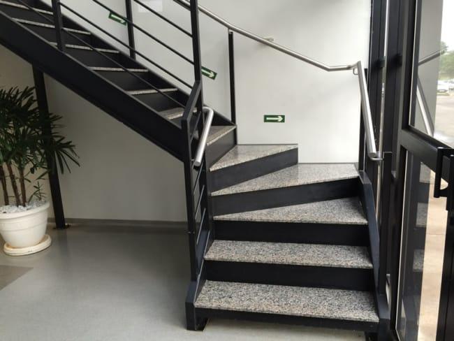 escada em L de metal preto com degraus em granito