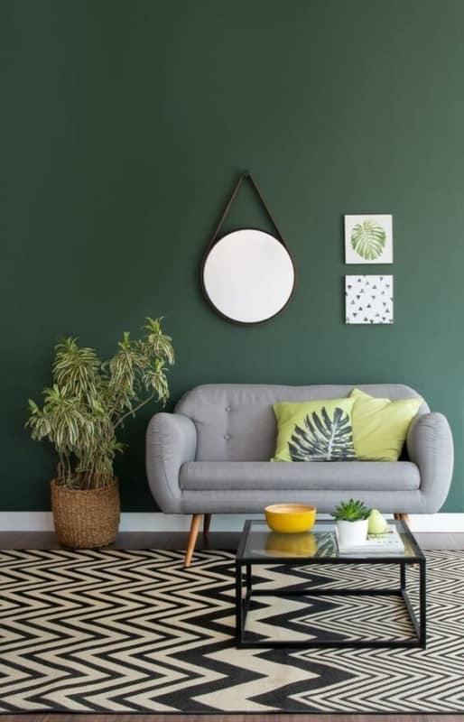 sala com parede verde escuro e sofa cinza