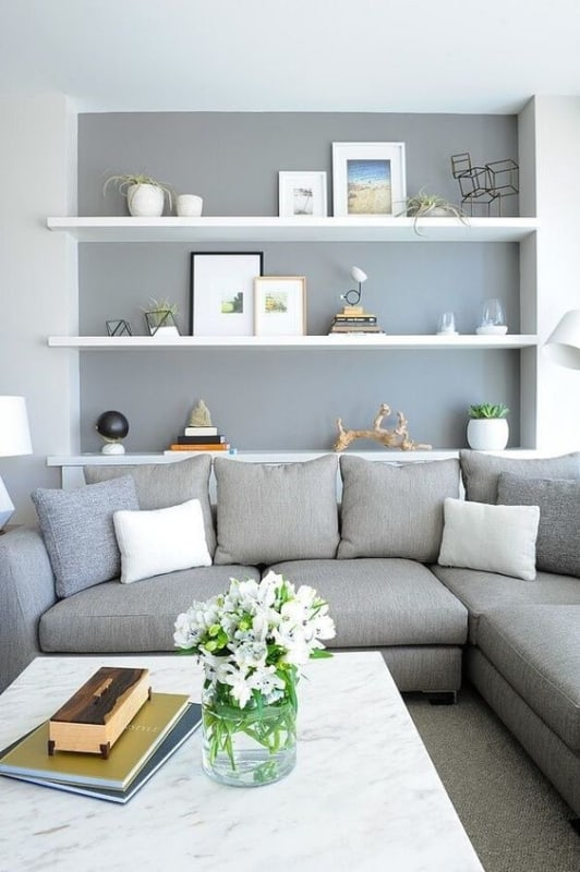 sala decorada com parede e sofa cinza claro