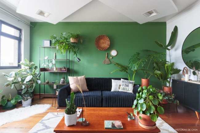 sala com parede verde e sofa preto