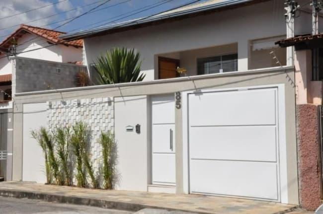 fachada de casa com portao fechado branco