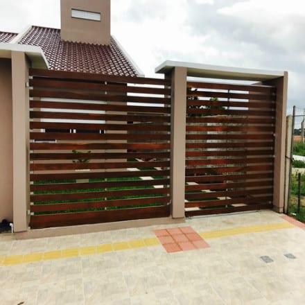 fachada de casa com portao de correr pequeno em madeira