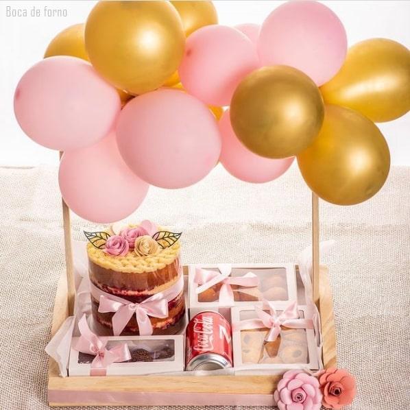 cesta de aniversario com bolo e bexigas