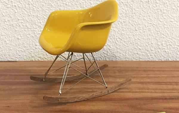 Cadeira Eames amarela no modelo de balanco