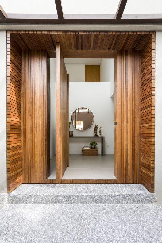 casa com porta de madeira pivotante na entrada