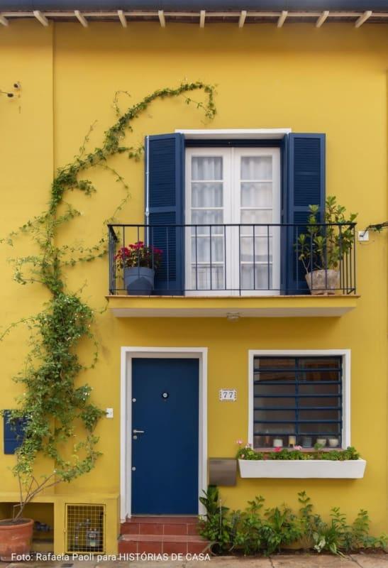 fachada de casa com porta de madeira azul