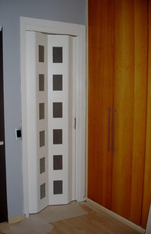 porta sanfonada branca de madeira com detalhes em vidro
