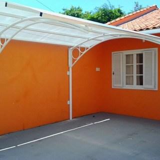 casa com toldo incolor de policarbonato