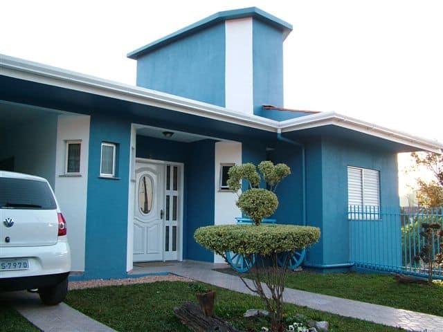 fachada de casa azul com porta de madeira branca