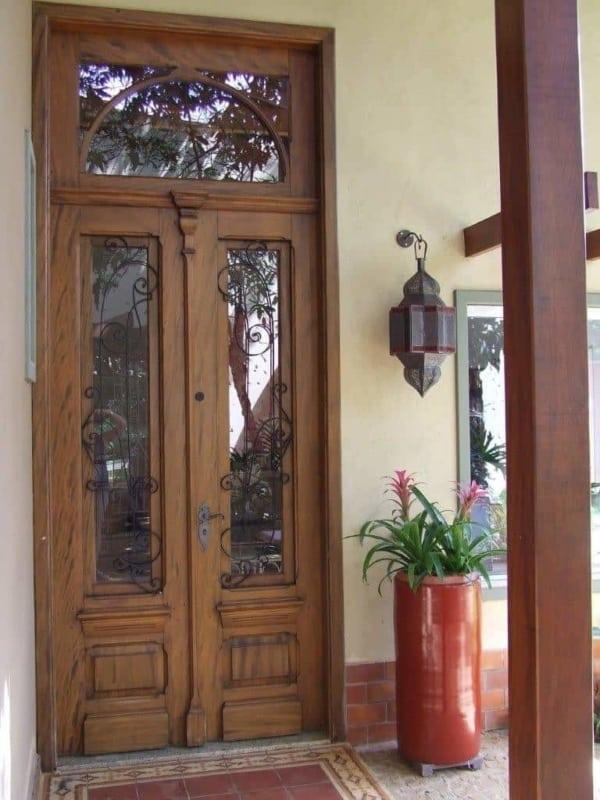casa com porta de entrada em madeira rustica e ferro fundido