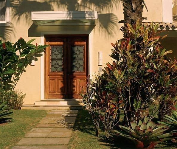 fachada de casa com porta de entrada de 2 folhas em madeira