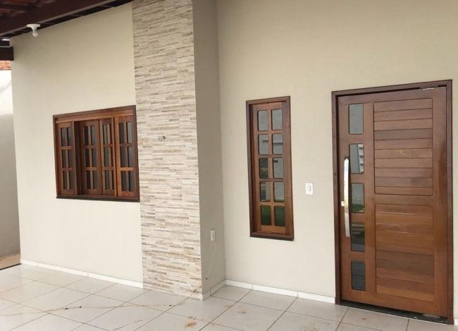 fachada de casa com porta de entrada em madeira e vidro