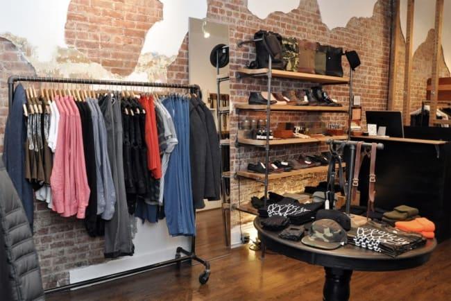 decoracao de loja pequena de roupas masculinas com parede de tijolinhos