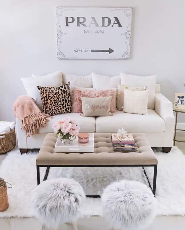 sala com quadro Prada e puffs e tapete de pelinhos