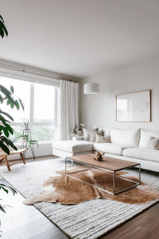 sala minimalista com dois tapetes embaixo da mesa de centro