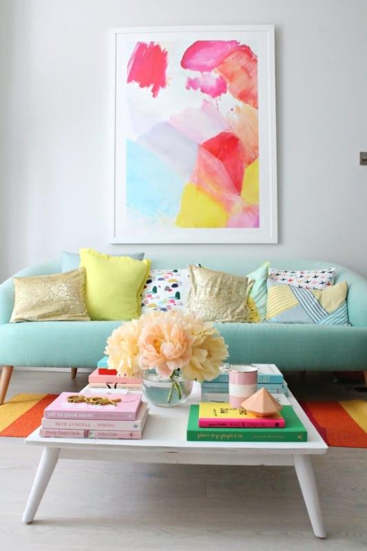sofa turquesa em harmonia com o tapete e o quadro na parede
