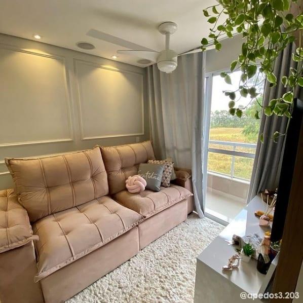 sala com sofa rosa e parede cromio