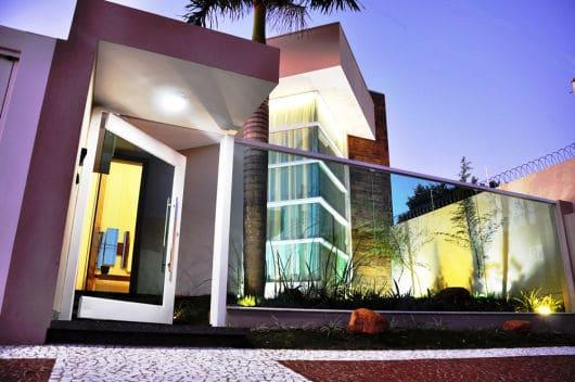 fachada de casa moderna com portao de vidro pivotante