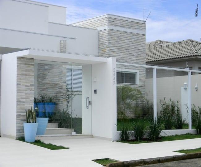casa com muro e portao pivotante de vidro