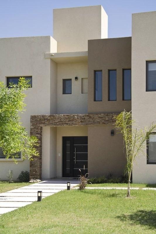 fachada de casa em cor palha e detalhes de pedras