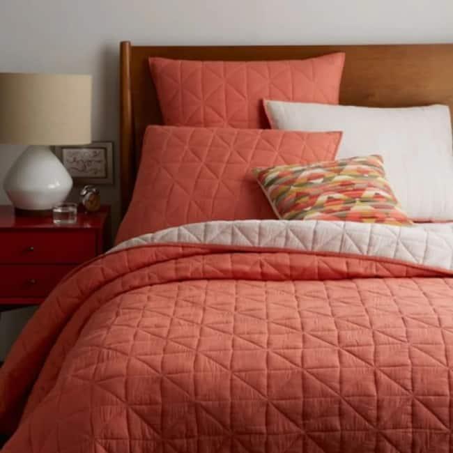 quarto com roupa de cama em cor goiaba