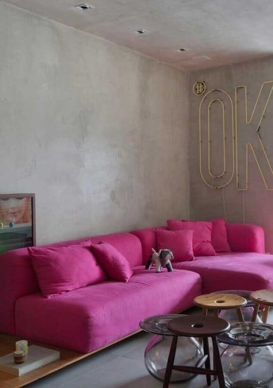sala com parede de cimento queimado e sofa magenta