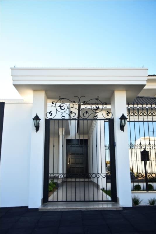 fachada de casa com portao social pivotante de ferro