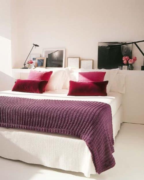 cama decorada com almofadas na cor magenta
