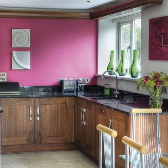 cozinha com armarios de madeira e parede magenta
