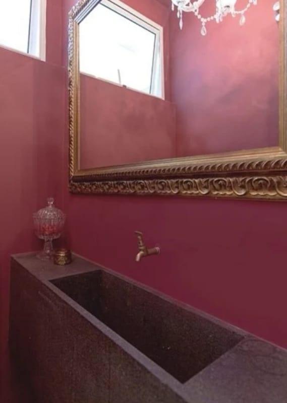 lavabo com parede marsala e espelho dourado