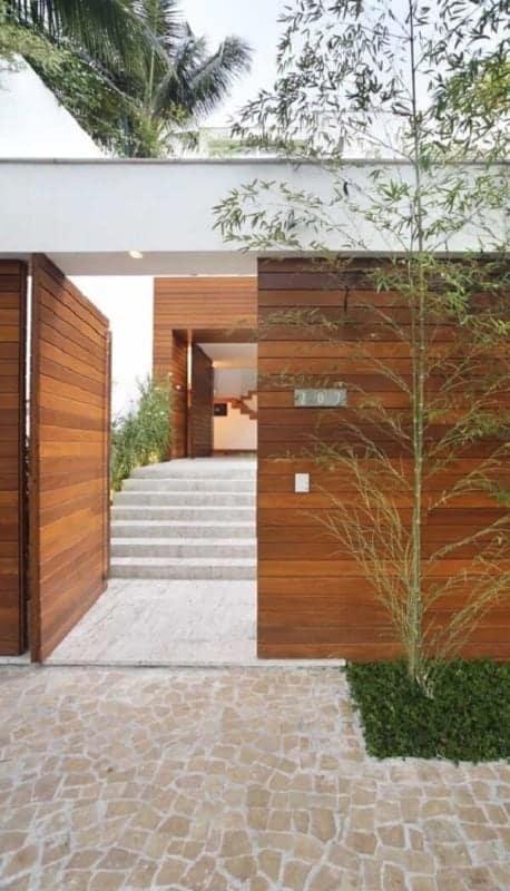 fachada de casa com portao moderno pivotante de madeira