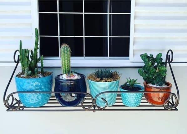 janela com floreira de ferro com vasinhos de plantas