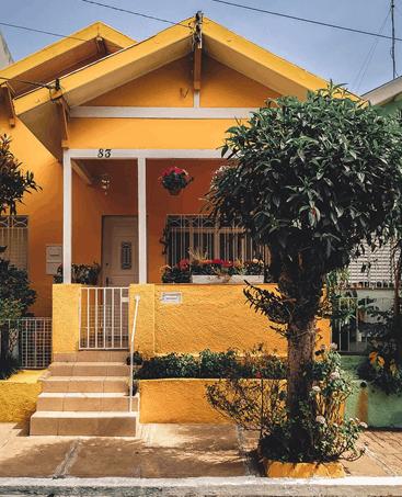 Casa com fachada amarela e varanda pequena